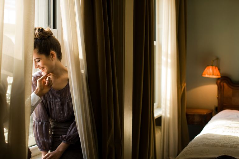 Affectionate couple standing near window in hotel room