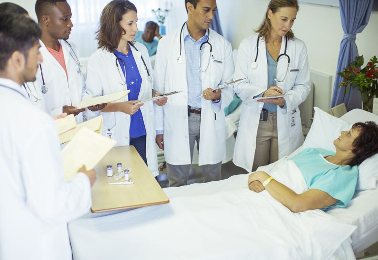 Doctor and residents examining patient in hospital