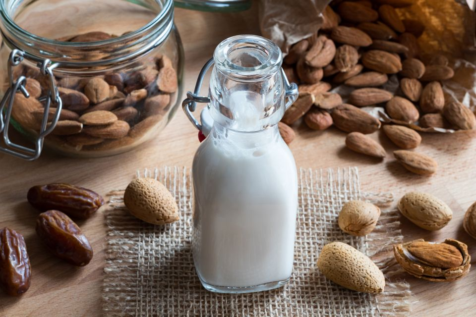 A bottle of almond milk with almonds