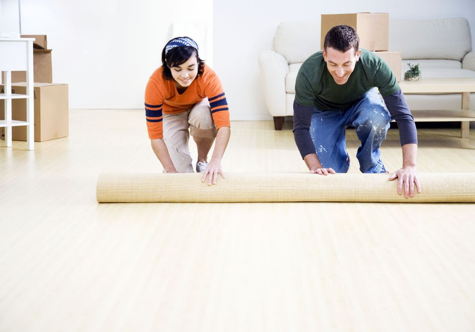 Couple unrolling carpet in their new home