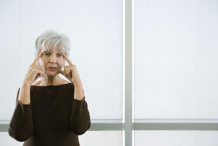 senior woman touching face due to tmj and headache pain