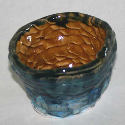 Coiled pot decorated with turquoise underglaze, and blue and honey-colored glazes.
