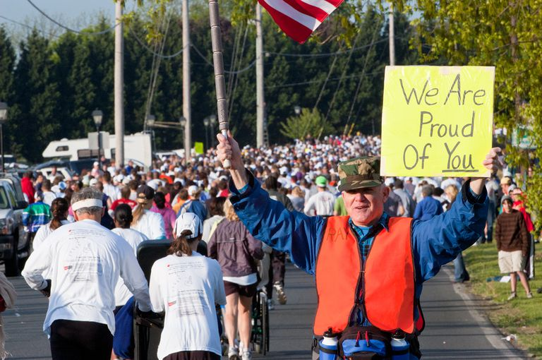Supporter Holds Sign Encouraging Runners at Marathon Start