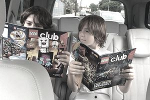 Two boys reading the free LEGO Life magazine.