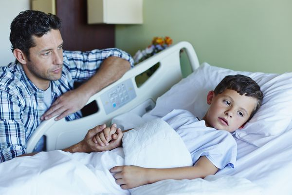 Tensed father looking at ill son in hospital