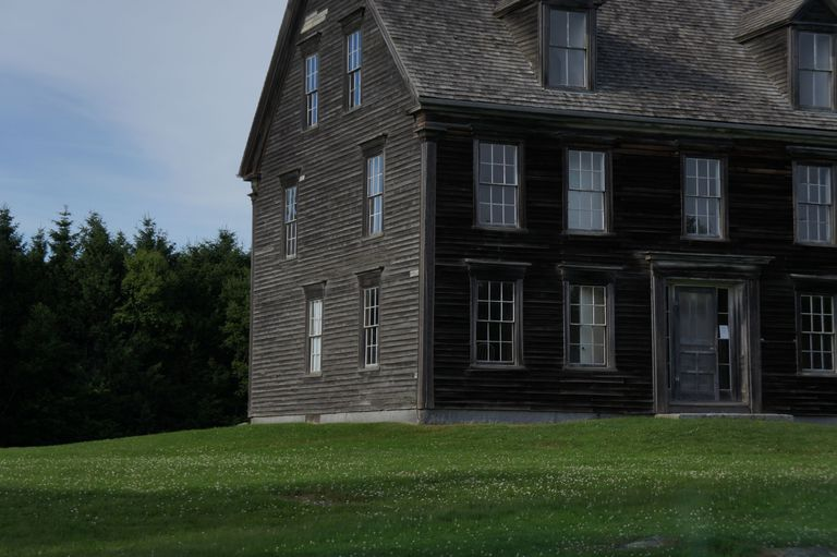 partial view of side-gabled farmouse, two stories, dark brown siding