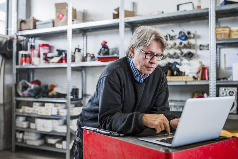 Mechanic using laptop at tire shop