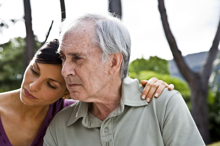 adult woman resting head on senior father's shoulder