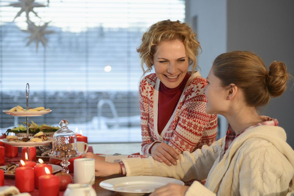Mid adult woman smiling at daughter at dinner table at Christmas time