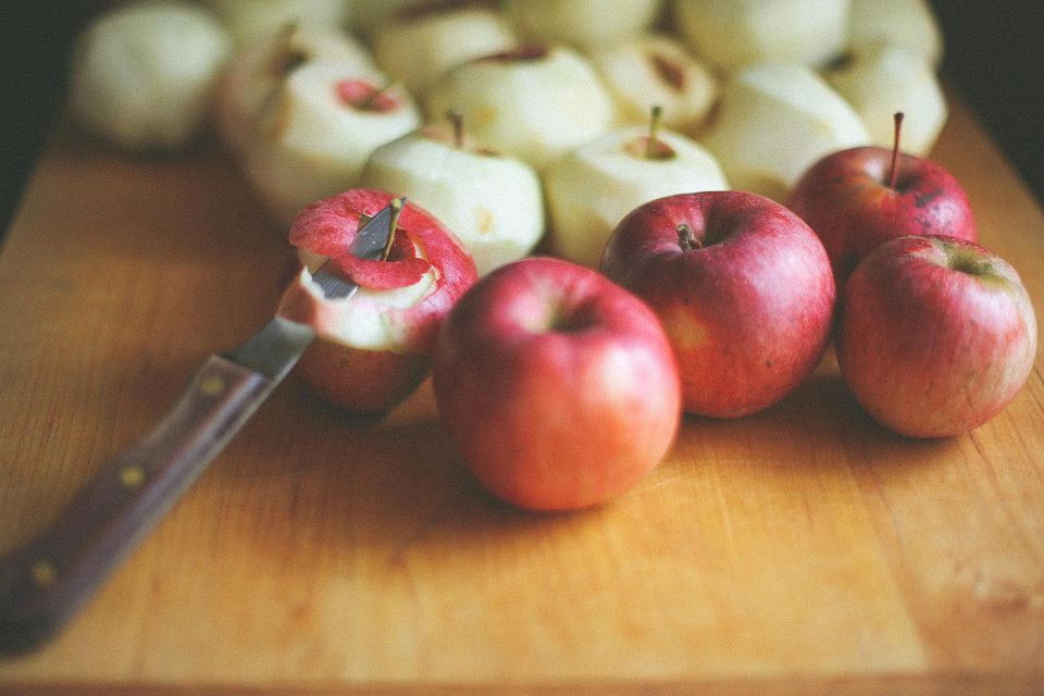 Peeled apples and a paring knife on a wood cutting board.