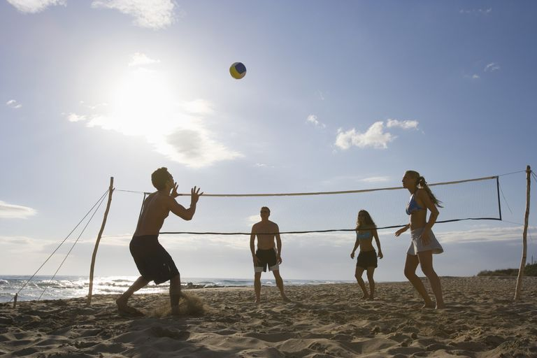 Young people playing beach volleyball
