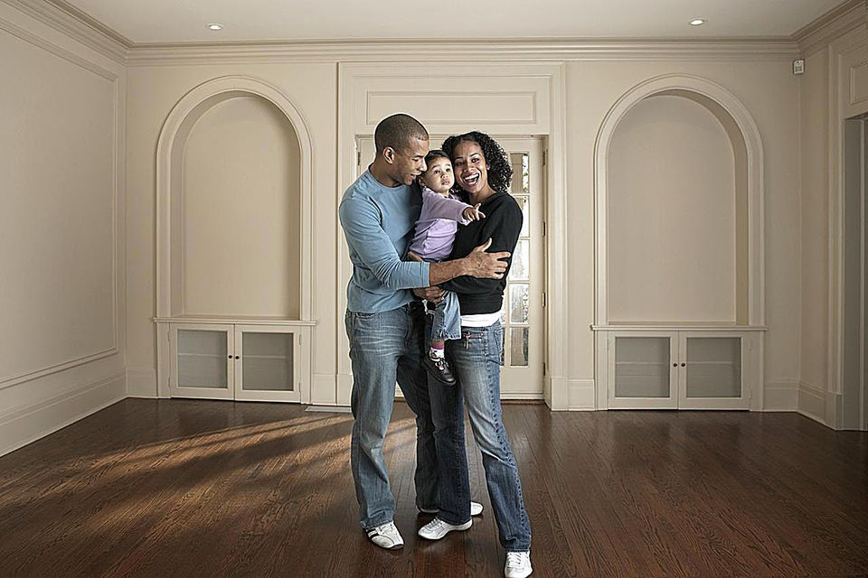 Couple holding baby girl (21-24 months) in barren room, smiling