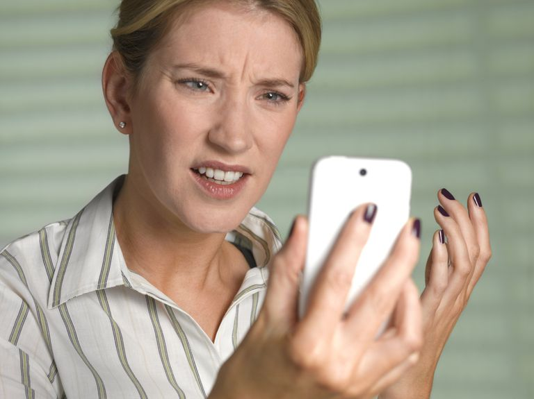woman with confused expression looking at cell phone