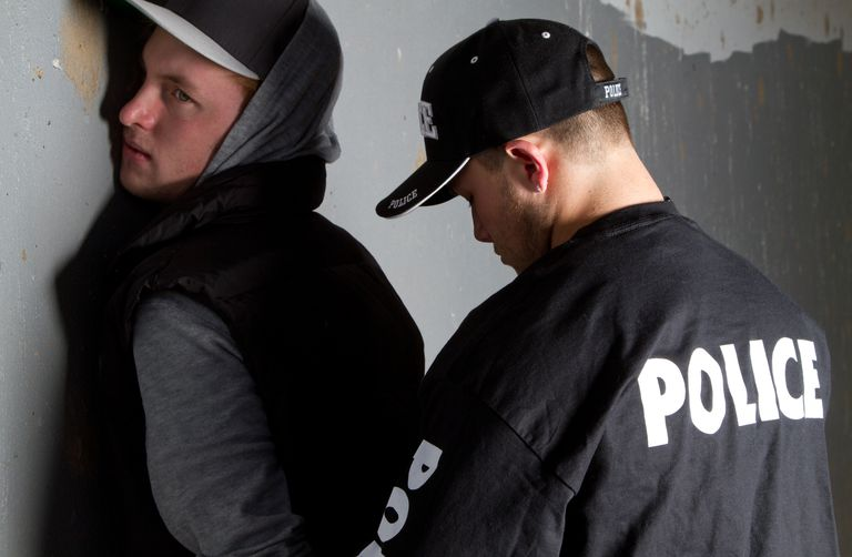 Man being handcuffed by a policeman against a gray wall