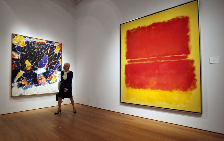 Woman looking at a red and yellow painting by Mark Rothko