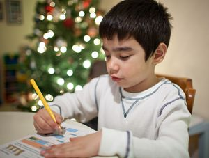 A boy completing a worksheet with a Christmas tree in the background.