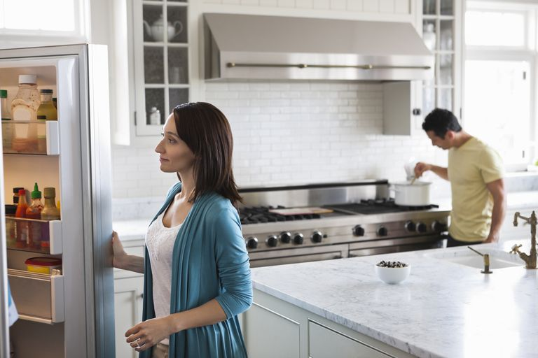 Woman looking in fridge in modern kitchen