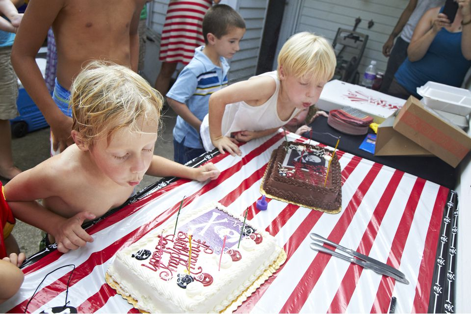 5 year old twin boys blowing out birthday candles.