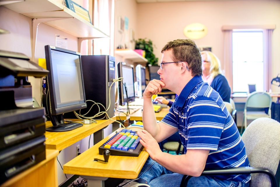 Young man with down syndrome, learning at computer