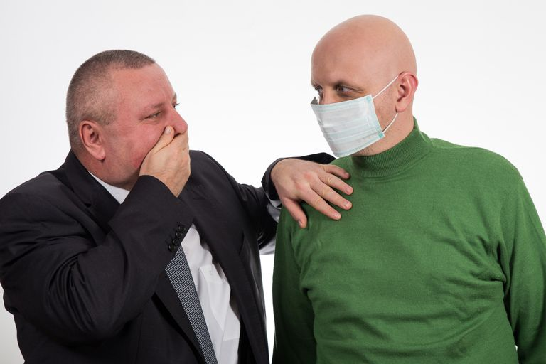 one man in a mask standing next to a man who is coughing