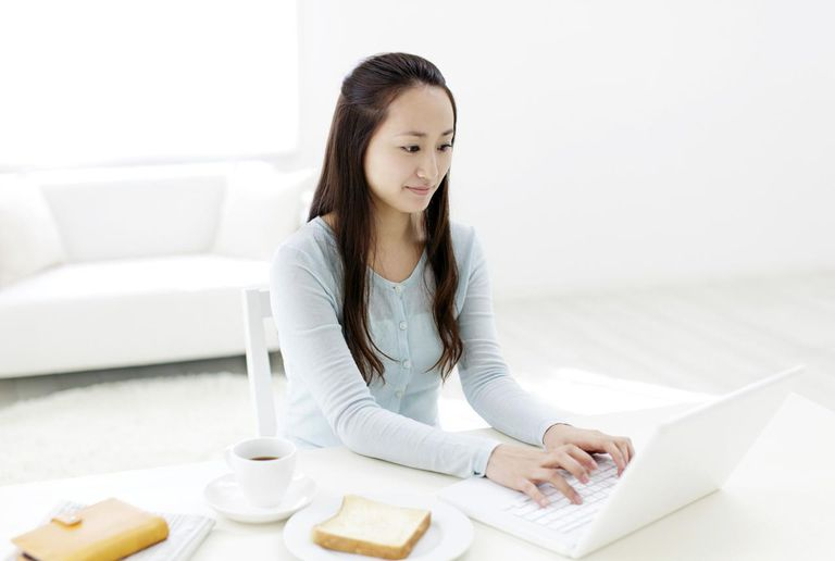 Young woman working on laptop in living room