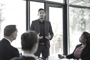 Man speaking to seated business people