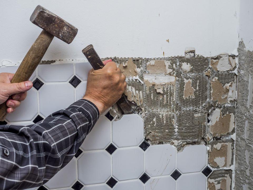 man removing ceramic tile