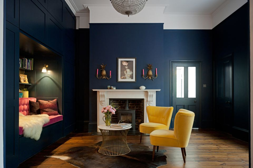 Bold blue living room with yellow and pink accents