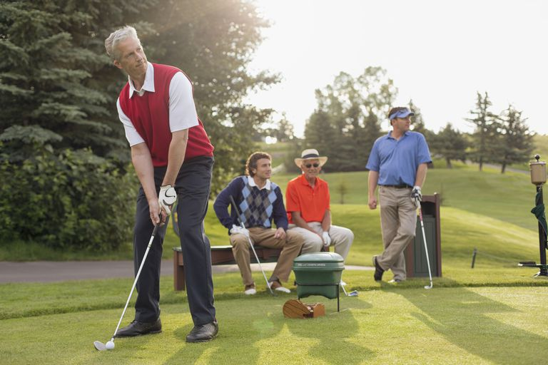 A foursome of golfers teeing off