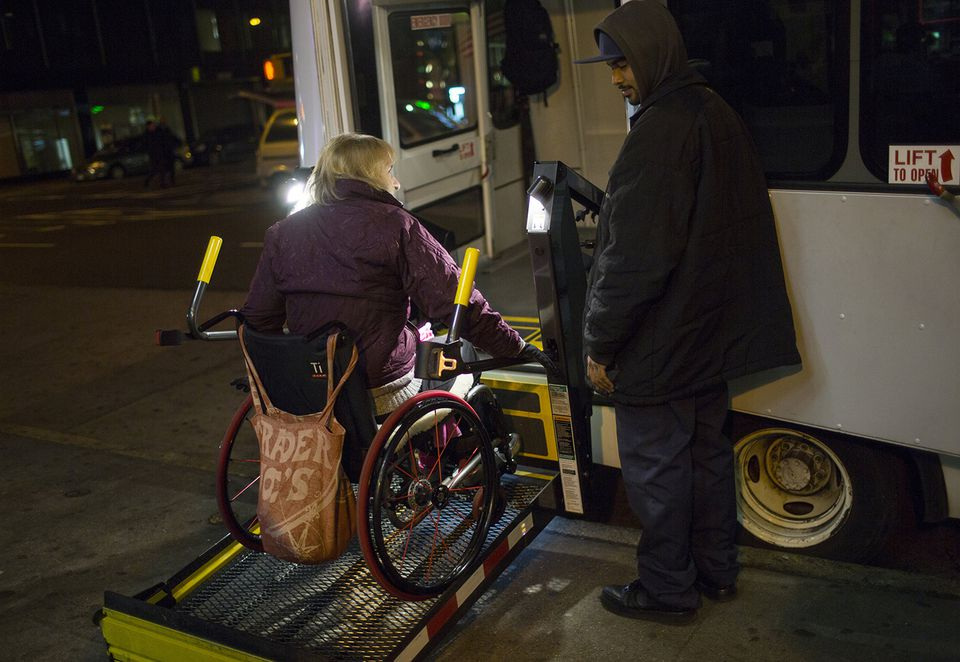 A woman in a wheel chair uses a special ramp January 5, 2013 to board a bus in the Brooklyn borough of New York.