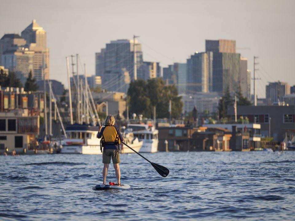 A woman paddles a paddleboard past houseboats on Lake Union near downdown Seattle.