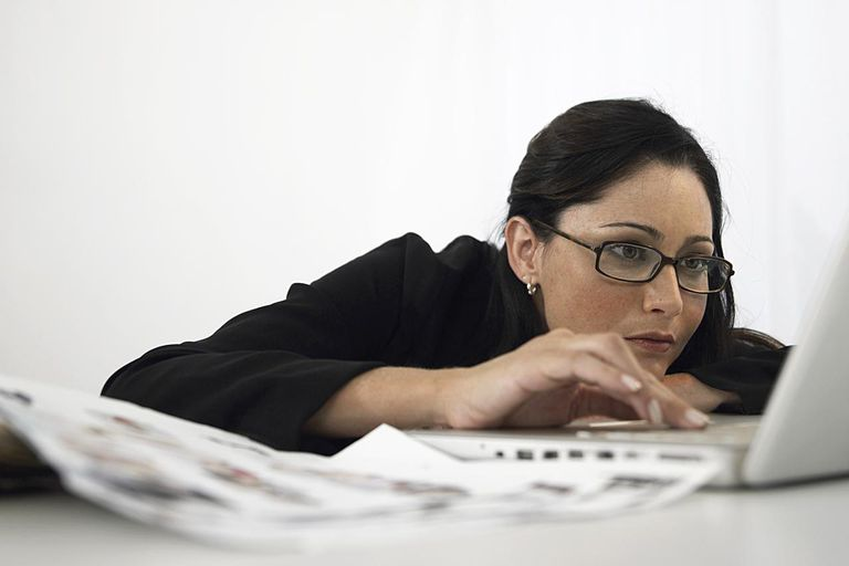Young businesswoman leaning on desk, using laptop