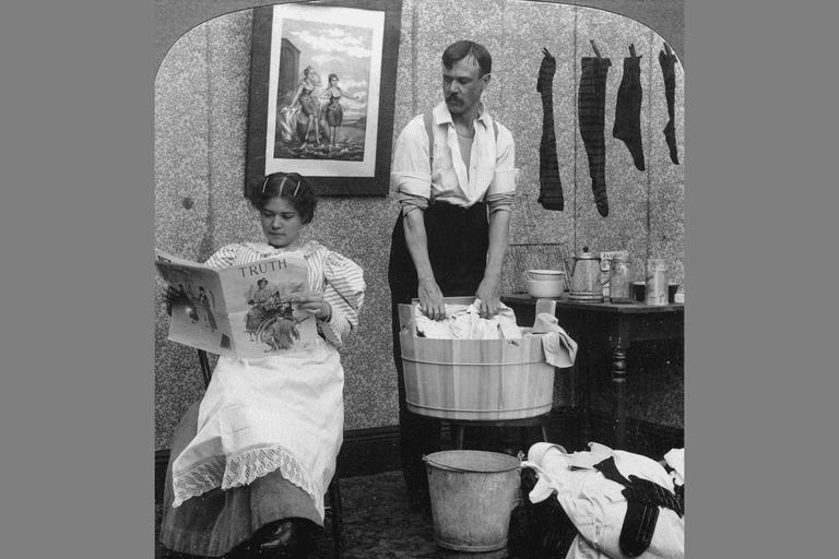 Role reversal: woman reading magazine, man doing the laundry