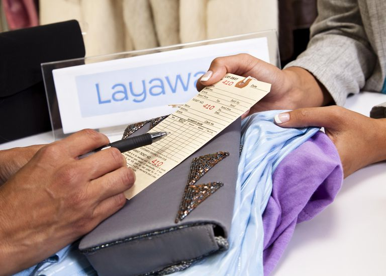 Shopper filling out layaway tag at checkout counter