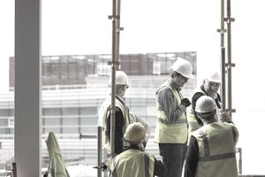 Workers on construction site conferring.