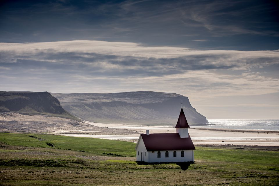 Wooden church framed against the Westfjord hills