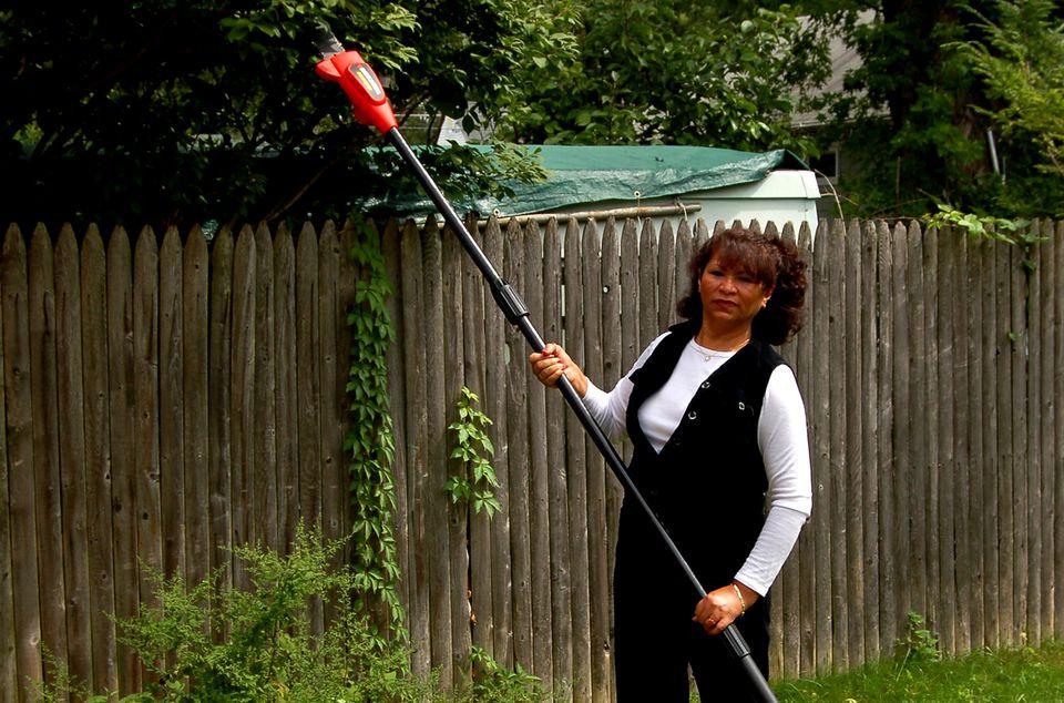 Woman holding Black & Decker pole chainsaw.