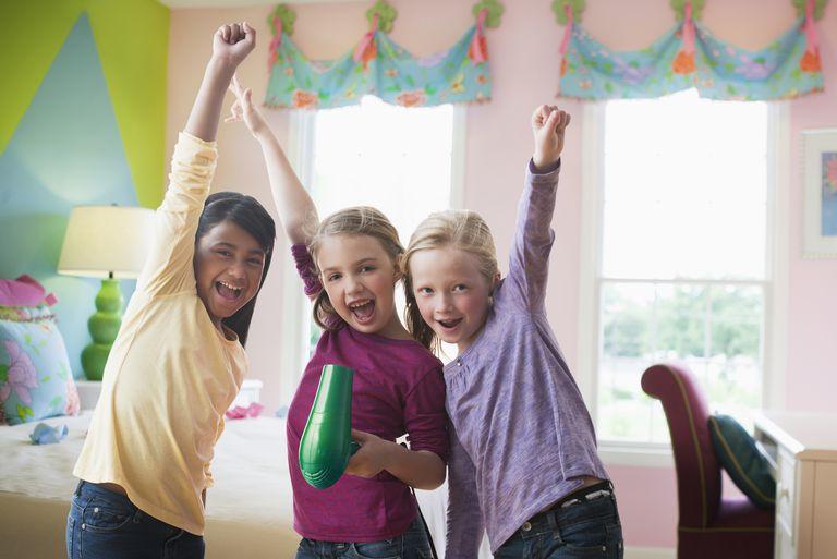 Girls singing with hair dryer in bedroom