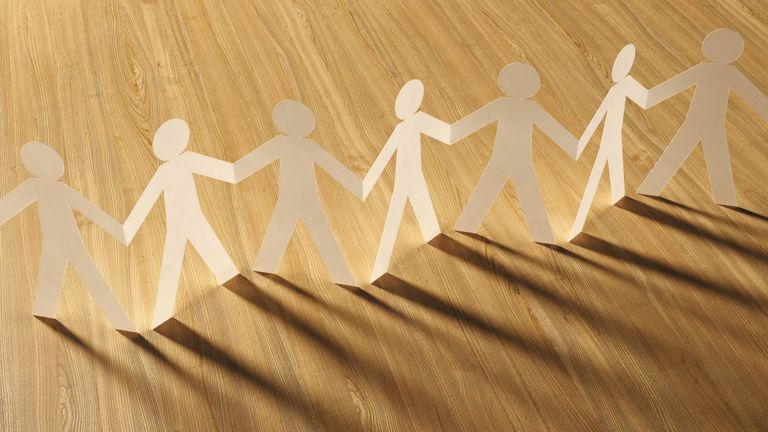 Photo of paper people standing on a wood floor