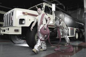 U.S. Airmen attach a hose too a fire engine.