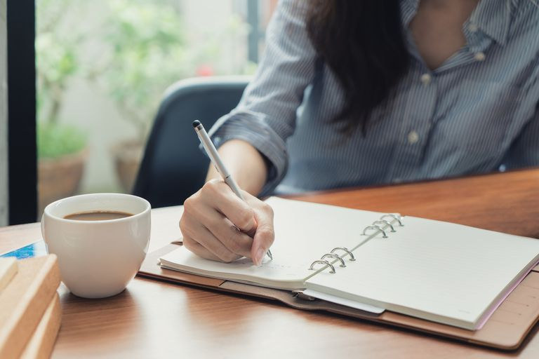 Close-up of young beautiful woman writing in notebook while sitting in chair in front of window at cafe.