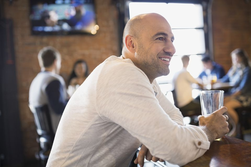 A man drinks at a bar