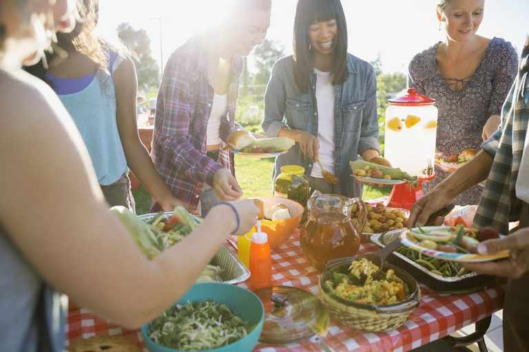 Smiling neighbors around potluck table in sunny park