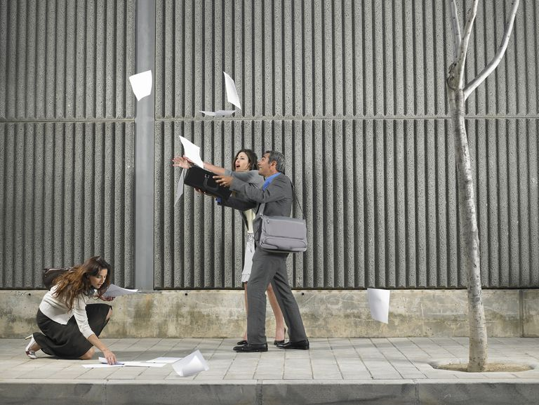 Wind blowing documents as people try to gather them on the street