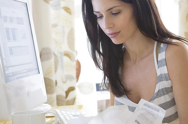 Woman calculating receipts at home