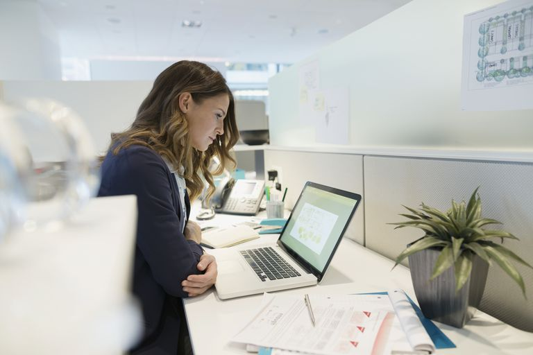 Focused young businesswoman working at laptop office