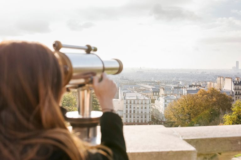 Woman looking at Paris through telescope