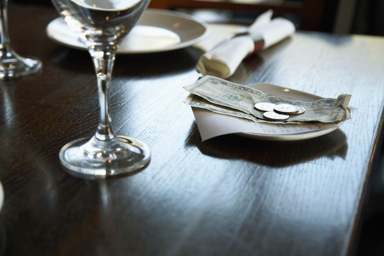 Dollar Bills and Receipt on Restaurant Table