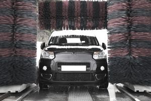 Black car traveling through an automatic car wash