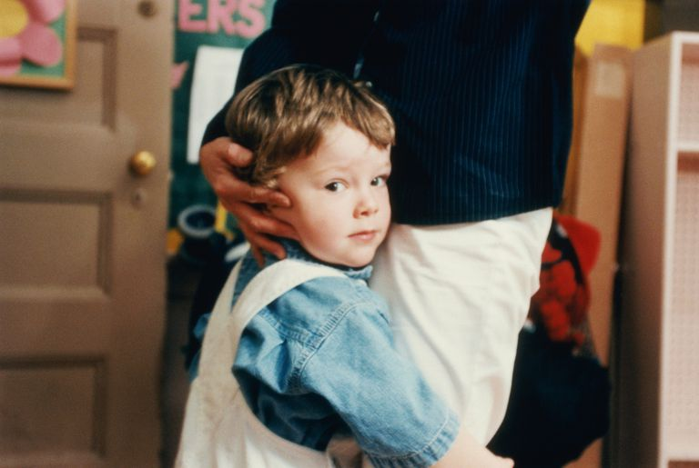 Boy (4-6) embracing mother's leg in classroom, portrait